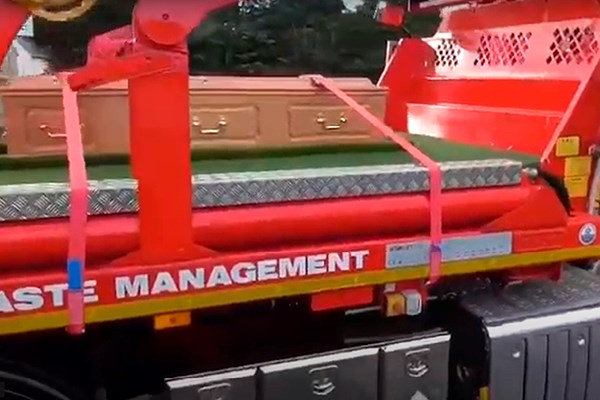 A sideview of flatbed lorry carrying a coffin   Dignity Funerals